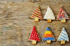 Покрашенные печенья рождественской елки на темной деревянной предпосылке Стоковая Фотография