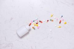 Покрашенные пилюльки с бутылкой на таблице Плоское положение Стоковое Фото