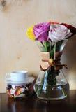 Покрашенные розы в баке кофе и белой чашке на стойке с высушенным flowerson на деревянной предпосылке Стоковая Фотография