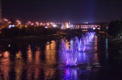 Покрашенные светящие фонтаны в середине озера вечером стоковые изображения rf