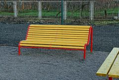 Покрашенные стойки деревянной скамьи на улице около загородки Стоковые Фото