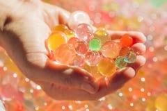 Покрашенные шарики воды отбортовывают, гидрогель внутри в руках Чувственные опыты стоковое фото rf