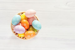Покрашенные яичка в корзине на белой предпосылке Стоковые Изображения