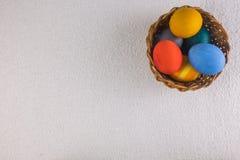 Покрашенные яичка в корзине, подготовленной на праздник пасхи Стоковые Фото