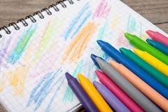 покрашенные crayons и пустая страница на деревянном столе Стоковое фото RF