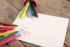 покрашенные crayons и пустая страница на деревянном столе Стоковая Фотография
