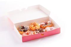 Покрашенные donuts с поливой в коробке изолированной на белизне Стоковые Фото