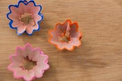 Покрашенные shavings карандаша в цветке формируют на деревянной предпосылке Стоковое Фото