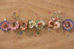Покрашенные shavings карандаша на деревянной предпосылке Стоковая Фотография