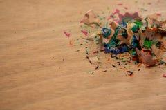 Покрашенные shavings карандаша на деревянной предпосылке Стоковое Изображение