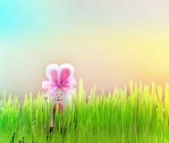 Покрашенный зайчик пасхального яйца на зеленой траве Стоковое Изображение