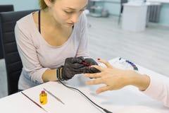Покрашенный маникюр, картина ногтя Manicurist женщины делая профессиональный маникюр, используя блеск геля цвета, ноготь и заботу стоковые фотографии rf