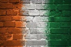 Покрашенный национальный флаг divoire Коута на кирпичной стене Стоковые Фото