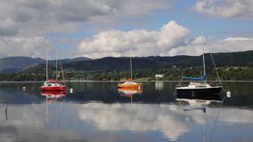 Покрашенный район Cumbria Англия Великобритания озера Ullswater парусников с горами и голубым небом на красивый день затишья все  акции видеоматериалы