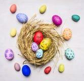 Покрашенный с сторонами яичек членов семьи декоративных для пасхи, в конце взгляд сверху предпосылки гнезда деревянном деревенско Стоковое Изображение RF