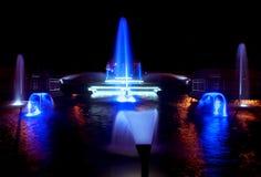 Покрашенный фонтан воды на ноче стоковое фото