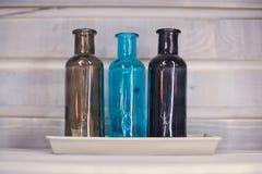 3 покрашенных декоративных бутылки голубая предпосылка Стоковые Изображения
