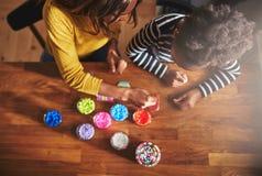 Покройте вниз с взгляда взрослого и ребенка выбирая шарики стоковое фото