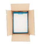 Покройте вниз с взгляда открытой картонной коробки с доской сзажимом для бумаги в ей Стоковые Изображения