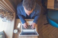 Покройте вниз с точки зрения бизнесмена работая на компьтер-книжке в кофейне Стоковые Фото