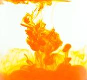 Покройте краской падение, оранжевое падение цвета в воде Облако чернил в воде на белой предпосылке Стоковые Изображения RF
