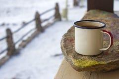 Покройте эмалью кружку на камне на деревянной веранде в зиме на деревенской предпосылке Стоковое Изображение RF