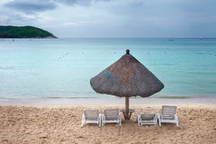 Покрыванный соломой зонтик с шезлонгами Стоковые Фотографии RF