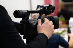 Покрывать случай с видеокамерой Фильмы Videographer с видеокамерой Оператор камеры работая внутри помещения стоковые фотографии rf