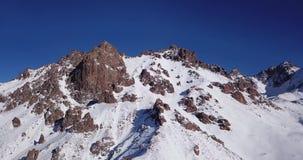 покрынный снежок гор Стрельба с трутнем Белый снег на серых и коричневых камнях сток-видео