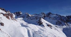 покрынный снежок гор Стрельба с трутнем Белый снег на серых и коричневых камнях видеоматериал