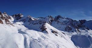 покрынный снежок гор Стрельба с трутнем Белый снег на серых и коричневых камнях акции видеоматериалы