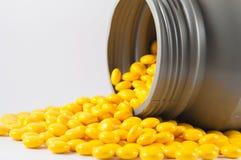 Покрытая желтая таблетка и серая пластичная бутылка на белизне стоковая фотография rf