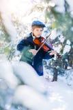 покрытая зима сказа снежка дома fairy пущи деревянная Милый скрипач мальчика в лесе зимы Стоковое Фото