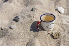 Покрытая эмалью кружка с чистой питьевой водой от Lake Baikal на береге озера в песке среди камней Стоковые Изображения