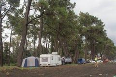 Покрытые караван, автомобили и шатер Туристы на празднике в лесе, устанавливая шатер покрытый стоковая фотография