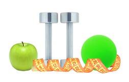 Покрытые хромом гантели фитнеса, лента измерения, шарик и зеленое яблоко Стоковые Фото
