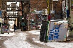 Покрытый граффити переулок искусства, наклоненный мусорный контейнер Стоковое Фото