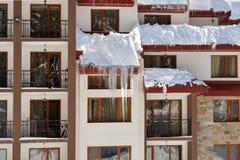 покрытый снежок дома Покрытый с снегом, вися сосульки льда Стоковые Фото