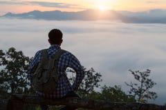 Покрыт турист с рюкзаком на наклоне горы, долина стоковое изображение rf