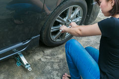 Покрышка женского водителя изменяя на ее сломленном автомобиле стоковые изображения