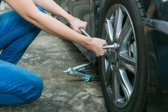 Покрышка женского водителя изменяя на ее сломленном автомобиле Стоковое Изображение RF