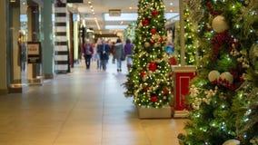 Покупатели рождества в запачканном торговом центре стоковое фото rf
