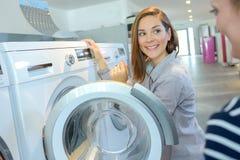 Покупатель выбирая стиральную машину в магазине бытового прибора Стоковые Фотографии RF