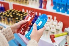 Покупатель женщины выбирает шампунь в магазине Стоковая Фотография