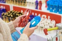 Покупатель женщины выбирает шампунь в магазине Стоковые Фотографии RF