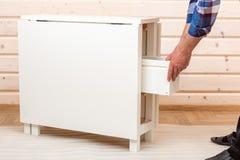 Покупатель собирает готов-к-собирает складной столик Готов-к-соберите мебель стоковые фото