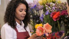 Покупатель флориста помогая мужской выбрать цветки видеоматериал