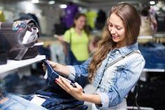 Покупатель женщины выбирая джинсы на магазине Стоковая Фотография