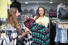 Покупатель женщины выбирая джинсы на магазине Стоковые Изображения