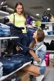 Покупатель женщины выбирая джинсы на магазине Стоковые Фото